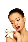 Beauty face of woman with lily flower. Royalty Free Stock Image