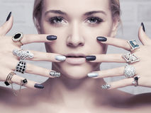 Beauty face.woman`s hands with jewelry rings. Beauty and fashion portrait of beautiful girl with make-up and manicure Royalty Free Stock Photography