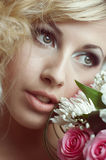 Beauty face of the young beautiful woman with flower. Stock Photography