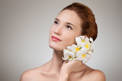 Beauty face of young beautiful woman with flower. Stock Photos