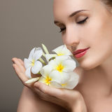 Beauty face of young beautiful woman with flower. Royalty Free Stock Image