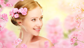 Beauty face of young beautiful woman with pink flowers in her ha stock photo