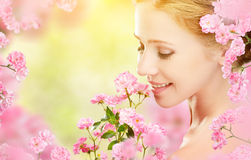 Beauty face of young beautiful woman with pink flowers in her ha. Beauty face of the young beautiful woman with pink flowers in her hair Royalty Free Stock Photography