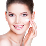 Beauty face of young woman with cosmetic cream on a cheek. Stock Image