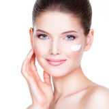 Beauty face of young woman with cosmetic cream on a cheek. Skin care concept. Closeup portrait isolated on white royalty free stock photo