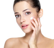 Beauty face of young woman with cosmetic cream on a cheek. Royalty Free Stock Photos