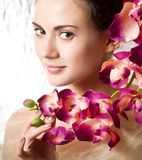 Beauty face of the young woman with flower Royalty Free Stock Photography