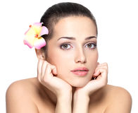 Beauty face of young woman with flower. Beauty treatment concept Royalty Free Stock Photo