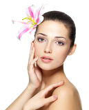 Beauty face of young woman with flower. Beauty treatment concept Stock Images