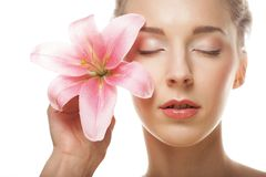 Beauty face of the young woman with pink lily Royalty Free Stock Photography