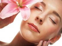 Beauty face of the young woman with pink lily Royalty Free Stock Images