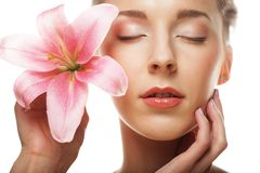 Beauty face of the young woman with pink lily Royalty Free Stock Photo