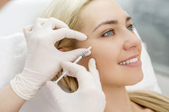 Beauty facial injections. Beautiful woman gets beauty facial injections. Face aging injection. Aesthetic Cosmetology Royalty Free Stock Photography