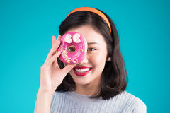Beauty fashion ASIAN model girl taking colorful donut over blue stock photography