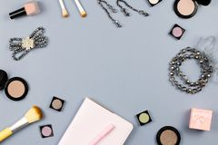 Beauty, fashion blogger concept. Fashion accessories, note book and cosmetics on grey background flat lay. Top view stock photos