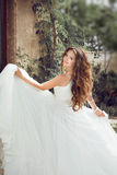 Beauty fashion bride girl gamboling with wedding blowing dress, Royalty Free Stock Images