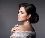 Beauty fashion bride makeup. Elegant fashionable woman portrait. Retro hair style. Brunette model with pearl earrings isolated on dark grey studio background Royalty Free Stock Images