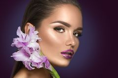Beauty fashion brunette girl with gladiolus flowers. Glamour woman with perfect violet trendy makeup royalty free stock photo