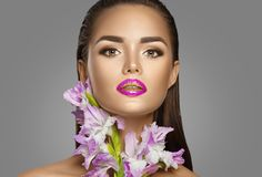 Beauty fashion brunette girl with gladiolus flowers. Glamour woman with perfect violet trendy makeup royalty free stock image