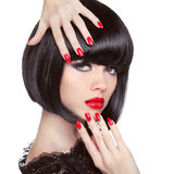 Beauty fashion brunette model portrait. Manicured nails.. Red lips. Professional makeup. Bob hairstyle. Trendy girl isolated on white studio background Royalty Free Stock Photos