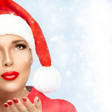 Beauty Fashion Christmas Woman in Santa Hat Looking Stardust Fal. Beautiful Christmas girl in Santa hat looking stardust falling. Red lips and manicure. Half Royalty Free Stock Images