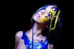 Beauty/fashion close up portrait of woman painted blue and yellow on black background Royalty Free Stock Photography