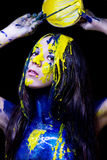 Beauty/fashion close up portrait of woman painted blue and yellow with brushes and paint  on black background Royalty Free Stock Image