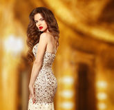 Beauty fashion elegant woman model in luxury dress with beaded a. Nd sequin. Attractive sensual girl posing in golden modern stylish interior stock photography