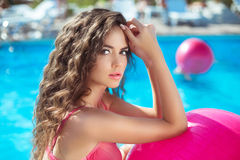 Beauty fashion girl Close up of sexy model with pink fitness bal. L in blue swimming pool on summer vacation Stock Image