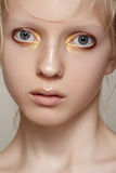 Beauty & fashion. Girl model face with bright holiday gold make-up, clean skin Stock Image