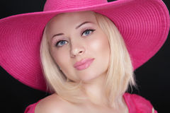 Beauty fashion girl portrait. Blond female in pink hat isolated. On black background Royalty Free Stock Photo