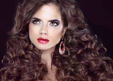 Beauty fashion girl. Wavy long hair. Brunette model with red lip Stock Images