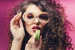 Beautiful girl eat green macaroon in confectionery dressing glasses royalty free stock photography