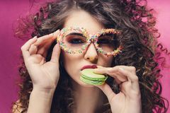 Beautiful girl eat green macaroon in confectionery dressing glasses stock image