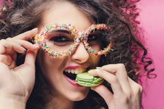 Beautiful girl eat green macaroon and smile in confectionery dressing glasses royalty free stock photo