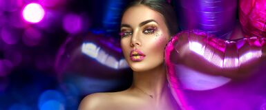 Beauty fashion model girl creative art makeup, over purple, pink and violet air balloons background. Woman face Make-up