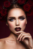 Beauty fashion model girl with dark makeup and roses in her hair Stock Image