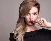 Beauty fashion model girl eating chocolate. Stock Image