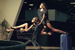 Beauty Fashion model girl. Fashion look. Fashion pretty cool girls in trolley cart Stock Photo