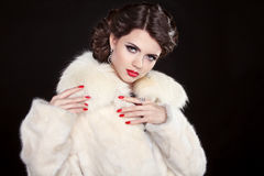 Beauty Fashion Model Girl in a Fur Coat with makeup and hair sty Stock Photo