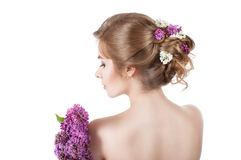 Beauty fashion model Girl with Lilac Flowers Hairstyle. Girl standing back. Stock Photos