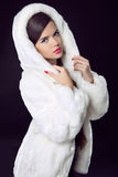Beauty Fashion Model Girl in Mink Fur Coat and white furry hood. Royalty Free Stock Image