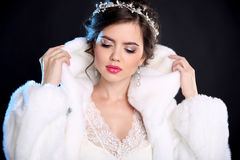 Beauty Fashion Model Girl in Mink Fur Coat and white furry hood. Makeup. Beautiful Luxury Winter Woman isolated on black background Royalty Free Stock Photo