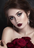 Beauty Fashion Model Girl Portrait with Red Roses.  Lips and Nails. Beautiful Luxury Makeup  Hair  Manicure Vogue Style Royalty Free Stock Images