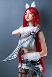 Beauty Fashion Model Girl with red wig and swords. On gray background. Cosplay Character from game Royalty Free Stock Image