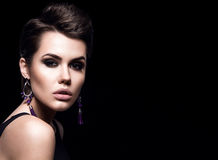 Beauty Fashion Model Girl with short hair. Brunette Model Portrait. Short haircut. Sexy Woman Makeup and Accessories. Isolated on black. Hair cut. Purple Royalty Free Stock Images
