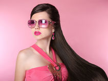 Beauty fashion model girl in sunglasses with bright makeup, long. Hair, luxury earrings jewelry. Glamour woman isolated on pink studio background royalty free stock image