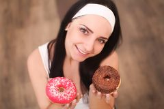 Beauty fashion model girl taking sweets and colorful donuts. Funny joyful styled woman with sweets on wood background. Diet, dieti Stock Image