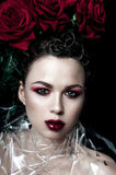 Beauty Fashion Model Woman face. Portrait with Red Rose flowers. Red Lips and Nails. Beautiful Brunette Woman with Luxury Makeup, Stock Photo