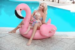 Beauty fashion mother with daughter family look. Beautiful blond. Women with having fun with little pretty gil wears in swim wear posing on Inflatable Flamingo stock photos